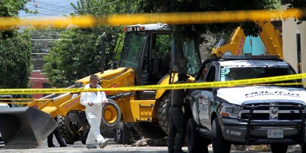 Personal forense trabaja en una escena de crimen donde se descubrieron 11 cuerpos enterrados.