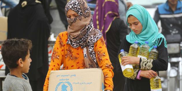 Mujeres cargando alimentos del programa de la ONU para Raqa, Siria, el 26 de abril de 2018. La pobreza si discrimina por género.