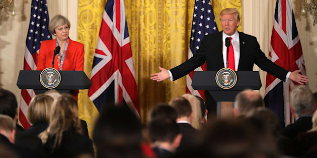President Donald Trump gestures toward British Prime Minister Theresa May during their news conference in the East Room of the White House in Washington, Friday, Jan. 27, 2017. (AP Photo/
