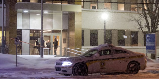 Police stand in the front doors of the courthouse in Maniwaki, Que. after two people were injured in a shooting there, on Wednesday, Jan. 31, 2018.