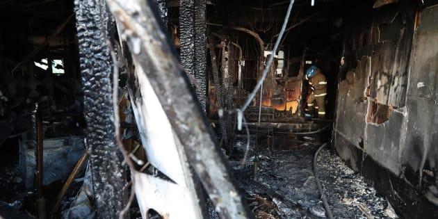 Los bomberos apagan los restos del fuego en un cuarto de hospital afectado.