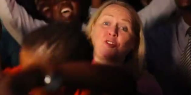A screengrab from a CBC News report shows correspondent Margaret Evans barely able to stand in front of the camera as crowds celebrate Robert Mugabe's resignation.