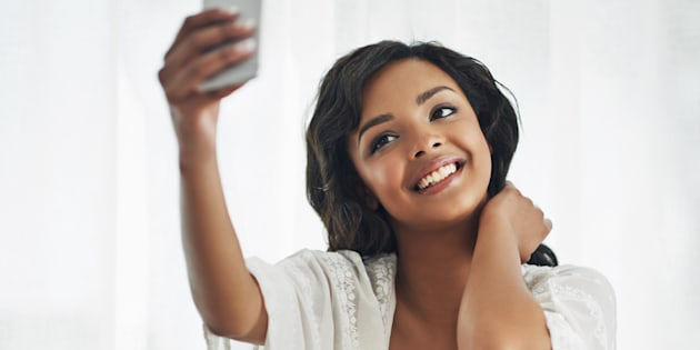 Shot of a beautiful young woman taking a selfie while relaxing in her bedroom