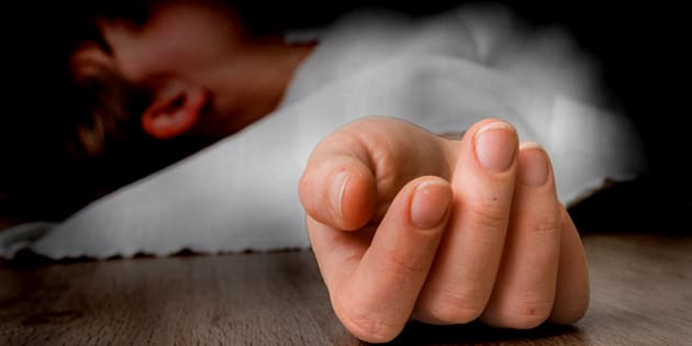 Dead woman lying on the floor under white cloth with focus on hand