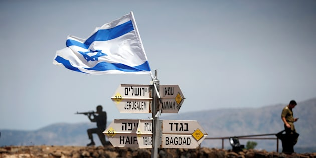 An Israeli soldier stands next to signs pointing out distances to different cities, on Mount Bental, an observation post in the Israeli-occupied Golan Heights that overlooks the Syrian side of the Quneitra crossing, Israel May 10, 2018. REUTERS/Ronen Zvulun     TPX IMAGES OF THE DAY