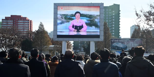 Pyongyang residents watch a big screen near the Pyongyang Railway Station showing the news on the successful launch of the new intercontinental ballistic missile (ICBM) Hwasong-15 in Pyongyang on November 29, 2017.