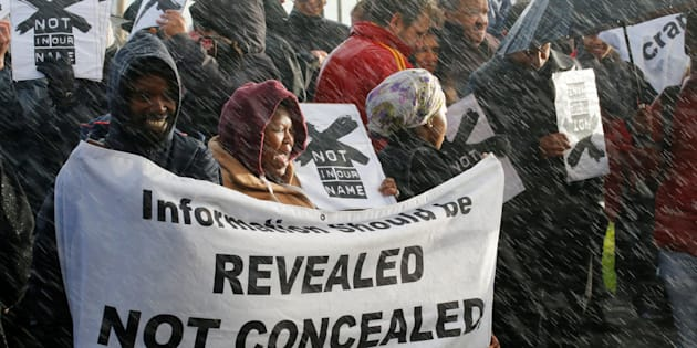 Demonstrators protest in the rain against the decision by public broadcaster the South African Broadcasting Corporation (SABC) that it would not broadcast scenes of violent protest, in Cape Town, South Africa, July 1, 2016.