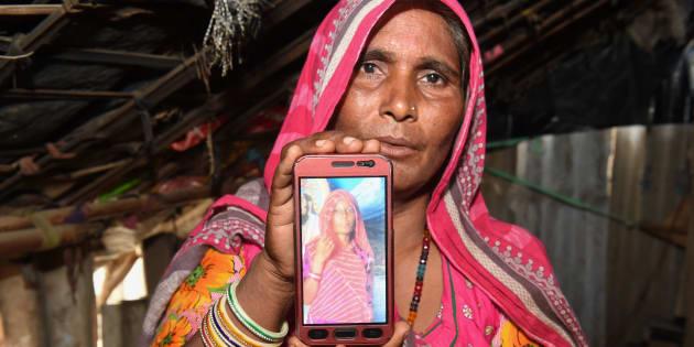 Mohinidevi Nath montre une photo de sa cousinen Shantadevi Nath, qui a été tuée par une bande qui croyait faussement qu'elle avait l'intention de kidnapper des enfants.
