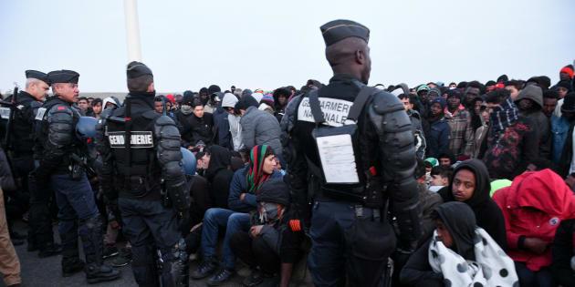 """Des policiers surveillent la foule de migrants attendant d'être évacuée de la """"Jungle"""" de Calais le 25 octobre 2016."""
