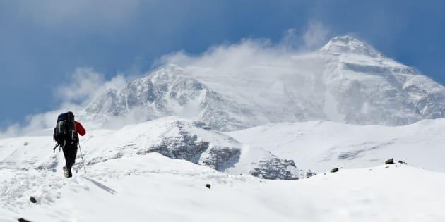 Man climbing up mountain at Mt. Everest.