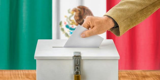 Un hombre deposita su voto en una casilla electoral.