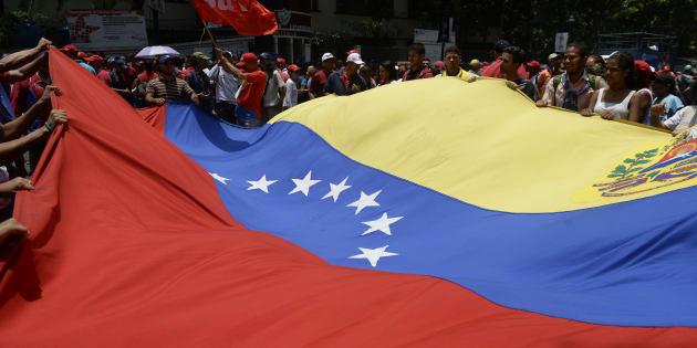 Los partidarios del presidente venezolano Nicolás Maduro portan una bandera nacional gigante durante un mitin en Caracas, Venezuela, el 26 de abril de 2017.