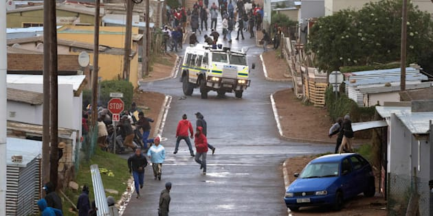 A South African Police armoured vehicle drives down a road dispersing protesters during clashes with police calling for the release of one of their colleagues, who was arrested for inciting violence, on July 13, 2018, in Hemanus.
