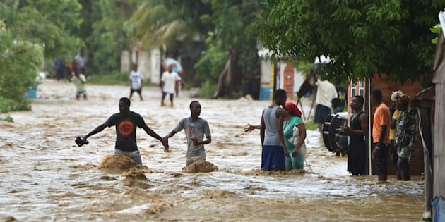 People try to cross the overflowing La Rouyonne river in the commune of Leogane, south of Port-au-Prince, Haiti,on Oct. 5.