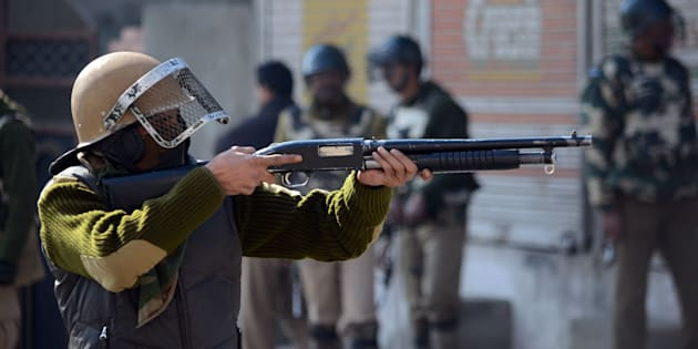 SRINAGAR, JAMMU AND KASHMIR, INDIA - 2016/02/05: A policeman points a pellet gun at protesters during pro-freedom demonstrations in old Srinagar, the summer capital of Indian controlled Kashmir.