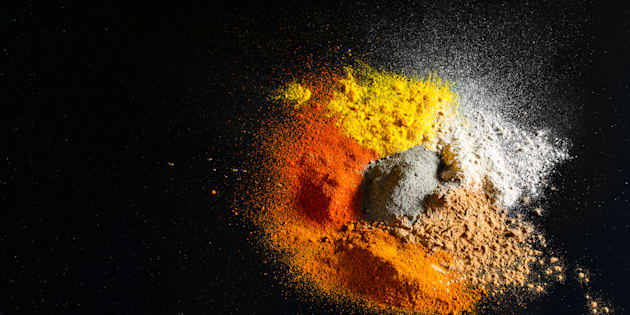 Spilled powder spices on black background - Abstract