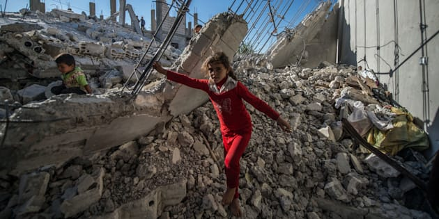 ALEPPO, SYRIA - OCTOBER 01: Children are seen on the rubble of a building in the Jarabulus district of Aleppo, Syria on October 1, 2016. Families, who returned to their homes back in Jarabulus after its cleansing from Daesh terrorist organization as part of the Operation 'Euphrates Shield', try to rebuild their houses before winter comes. The anti-Daesh operation called Euphrates Shield, which was launched on August 24, aims at improving security, supporting coalition forces, supporting Syrias territorial integrity and eliminating the terror threat along Turkeys border through Free Syrian Army (FSA) fighters backed by Turkish armor, artillery, and jets. (Photo by Halil Fidan/Anadolu Agency/Getty Images)