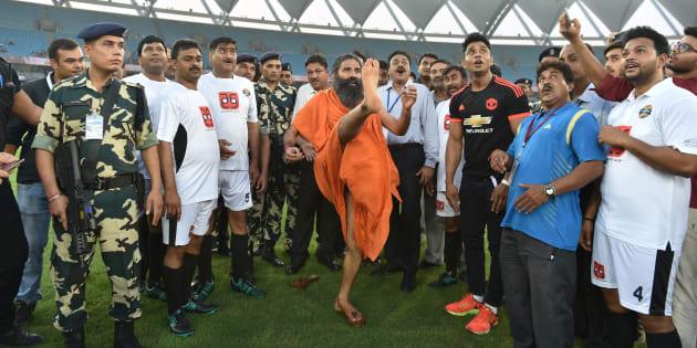 Indian yoga guru Baba Ramdev kicks a football ahead of a charitable football match in New Delhi.