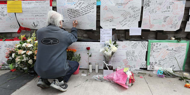 Jack Young leaves a note on a makeshift memorial for victims in the van attack in Toronto on April 24, 2018.