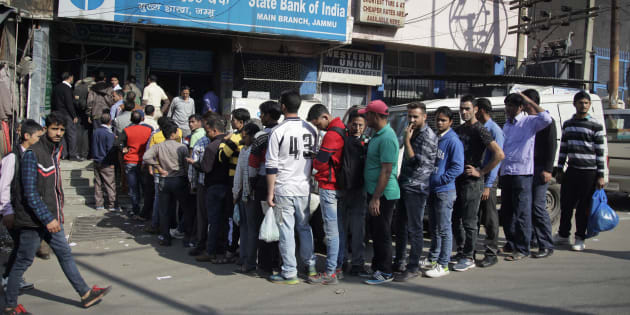 People wait in a queue to deposit or exchange discontinued currency notes outside a bank.
