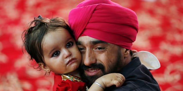 An Afghan Sikh holds his child inside a Gurudwara, during a religious ceremony in Kabul, Afghanistan June 8, 2016.