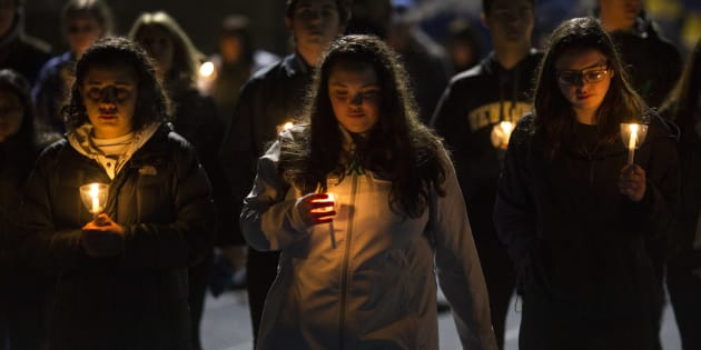 NEWTOWN, CT - FEBRUARY 23: Led by high school students, mourners walk around the track of the football field with candles during a community vigil at Newtown High School for the victims of last week's mass shooting at Marjory Stoneman Douglas High School in Parkland, Florida, February 23, 2018 in Newtown, Connecticut.