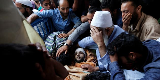Family members and relatives mourn next to the body of Burhan Wani, a separatist militant leader, during his funeral in Tral, south of Srinagar, July 9, 2016.