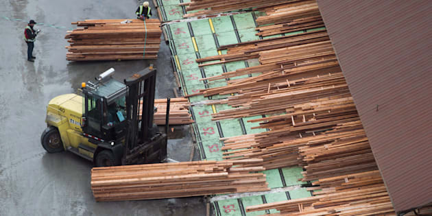 Workers sort and move lumber at the Delta Cedar Sawmill in Delta, B.C., on Jan.  6, 2017.