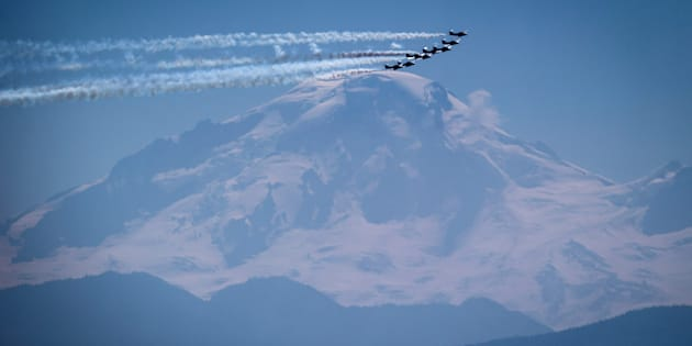Planes fly past Mount Baker in Washington State before landing at Abbotsford International Airport for the Abbotsford International Airshow.