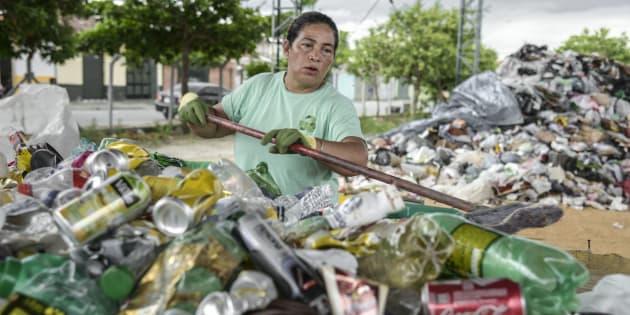 Trabalhadora separa alumínio de lixo em uma cooperativa. Mulheres são maioria em trabalhos precarizados.
