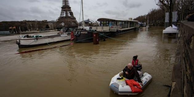 Varias personas usan lanchas para ser evacuadas en el Sena, con la Torre Eiffel de fondo.