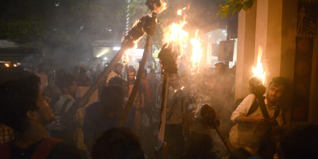 Activists participate in a torch rally against the communal violence in Bengal.