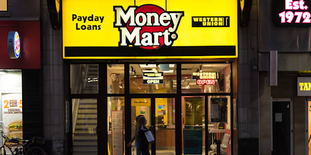 People walking in front of a Money Mart store in Toronto.