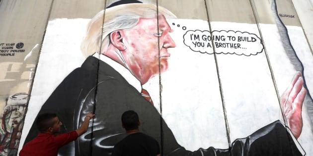 Dos hombres observan el grafiti dedicado al presidente Donald Trump en el muro israelí, a su paso por Belén (Cisjordania).