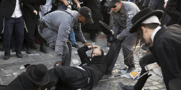 Varios policías israelíes se enfrentan a judíos ultraortodoxos que bloqueaban varias vías del tranvía durante una protesta de hoy contra el reclutamiento militar, en Jerusalén.