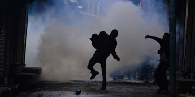 File photo of a boy pelting stones at police personnel amidst heavy tear gas smoke.