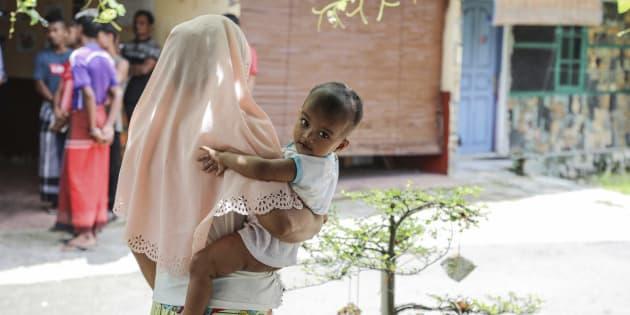 Una refugiada perteneciente a los rohingyas sostiene a su hijo en un refugio en Medan (Indonesia).