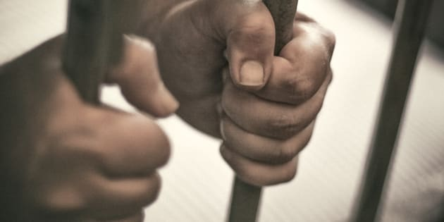 Man's hands tightly holding the bars of his jail cell.