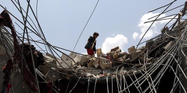 Varias personas inspeccionan un edificio tras el ataque aéreo de ayer en Saná (Yemen).