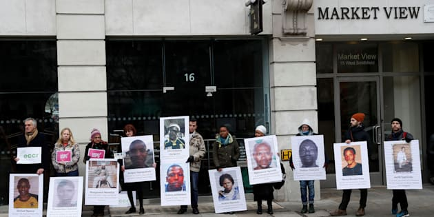 Demonstrators hold placards during a protest to demand victim compensation and improved worker living conditions for Marikana miners, outside Lonmin's annual general meeting in London, Britain January 26, 2017.