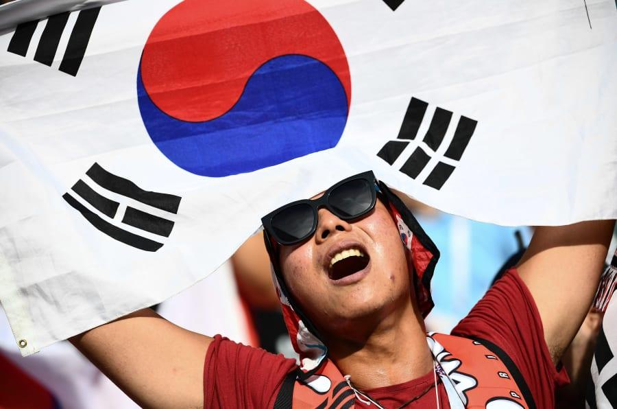 Una fan de Corea ondea una bandera de su país durante el partido Corea-Alemania.