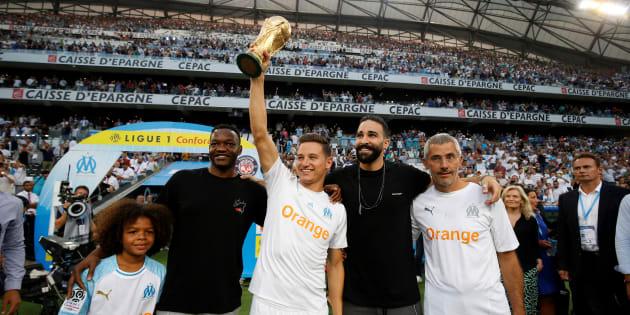 Florian Thauvin, Adil Rami et Steve Mandanda avec la Coupe du monde au stade Vélodrome le 10 août 2018.