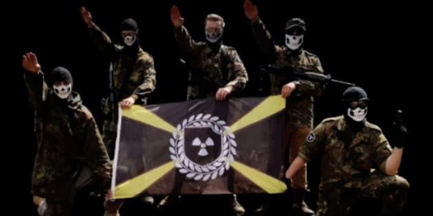 Des membres de la division Atomwaffen, un groupe néonazi violent, posent avec leur drapeau à thème nucléaire.