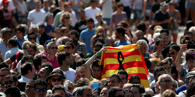 A man holds a Catalan flag as people gather to osberve a minute of silence at Placa de Catalunya, a day after a van crashed into pedestrians at Las Ramblas, in Barcelona, Spain August 18, 2017. REUTERS/Susana Vera