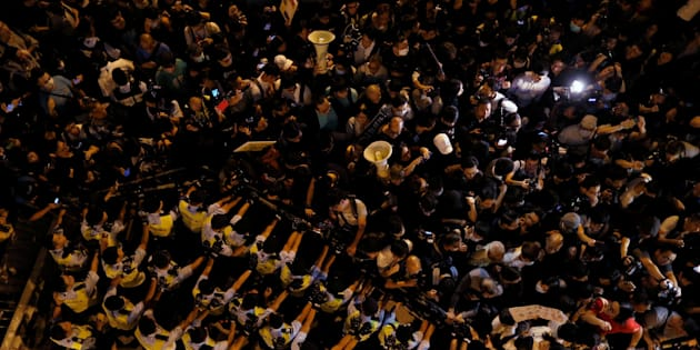 Police stop demonstrators as they protest against what they call Beijing's interference over local politics and the rule of law.