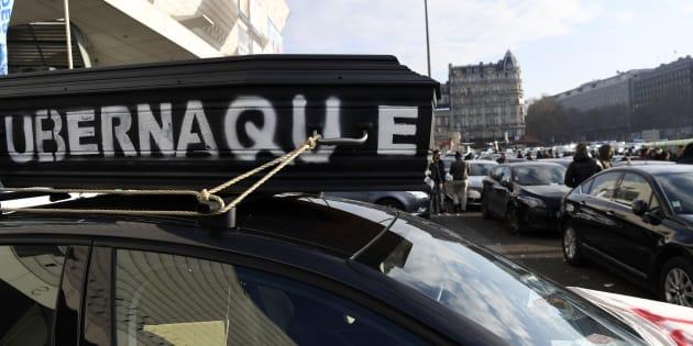 """Un faux cercueil sur lequel est écrit """"Ubernaque"""" est placé sur la voiture d'un chauffeur VTC à Porte Maillot à Paris le 15 décembre 2016. Les chauffeurs VTC revendiquent une meilleure rémunération et protestent contre les plateformes de réservation, dont Uber."""