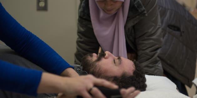 Aymen Derbali, une victime de l'attentat de Québec aujourd'hui paraplégique, suivant des exercices de rééducation. Le jour de l'attaque, Derbali a reçu sept balles, l'une d'entre elles atteignant sa colonne vertébrale,