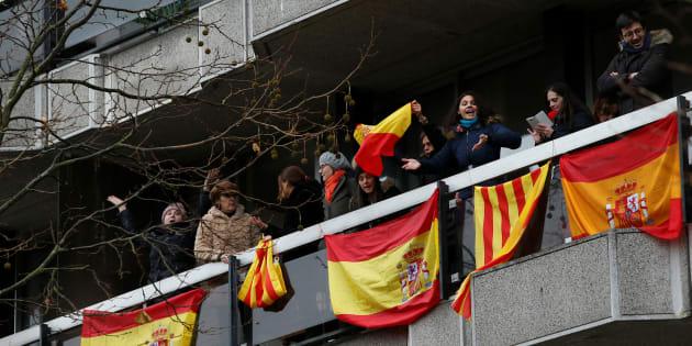 Varias personas sacan banderas de España y de Cataluña a su balcón en Bruselas.