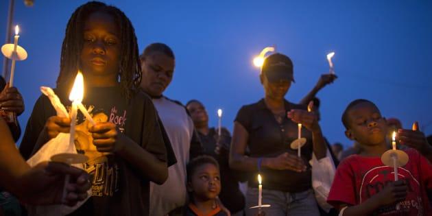 Des gens se rassemblent pour une veillée éclairée aux chandelles contre la violence armée dans le quartier d'Englewood à Chicago, Illinois, États-Unis, le 3 juillet 2015.