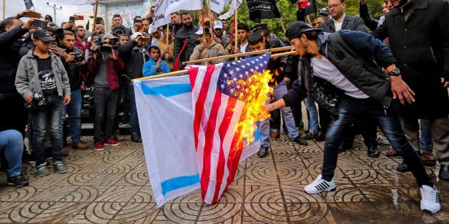 Un manifestante palestinese intento stamane a bruciare la bandiera Usa e quella di Israele a Gaza